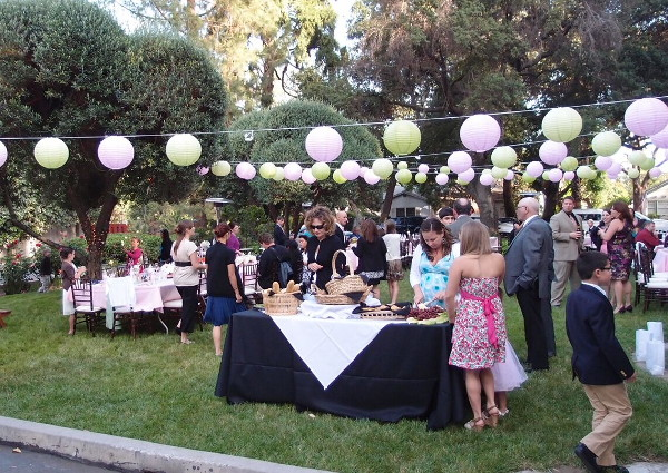Colorful lanterns and guests decorate the lawn
