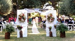 Bride with long train and her groom at the end of the aisle in our serene outdoor chapel